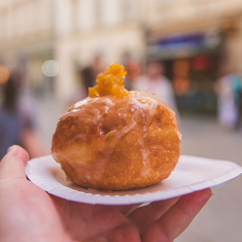 "The pączki (pronounced kind of like ""ponch-ki"") is Poland's version of the doughnut but with a richer dough that's usually punched up with a little alcohol. You'll usually find it deep fried, covered with glaze, and topped with orange zest. We had the lemon and rose versions from Placki Ziemniaczane right outside of Krakow's Main Square, and they were phenomenal. Crisp on the outside, squishy on the inside, and not a bit oily."