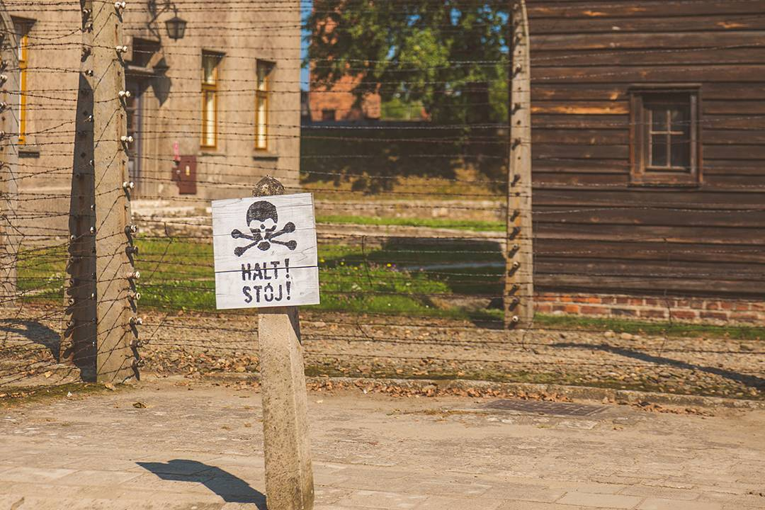 A sign outside of the Auschwitz barracks, right below one of the guard towers.