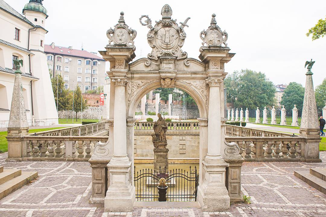 At the Church of St. Michael the Archangel and St. Stanislaus Bishop and Martyr and Pauline Fathers Monastery, Skałka, the legend goes that Bishop Stanisław criticized King Bolesław in the year 1079, so the king had his guards tear the bishop limb from limb and throw his body parts thrown in the pool beyond this gate. But four eagles watched over the body, and the limbs miraculously reattached themselves to the body. Whatever the story, the gate's really pretty.